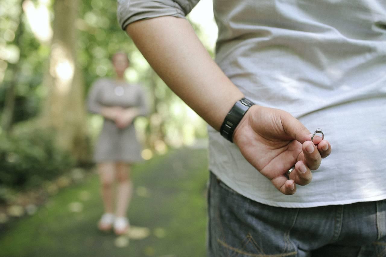 Młody mężczyzna chowa pierścionek zaręczynowy za plecami