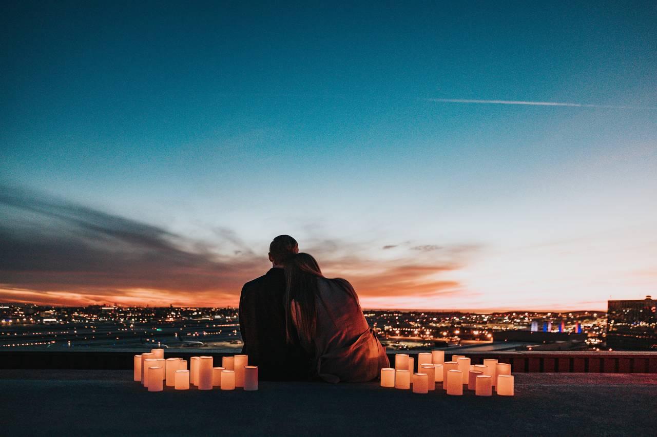 Młode małżeństwo siedzi wblasku świec nadachu budynku wtrakcie swojej podróży poślubnej