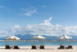 tanie wakacje spędzone na leżakach z parasolami z widokiem na morze i góry