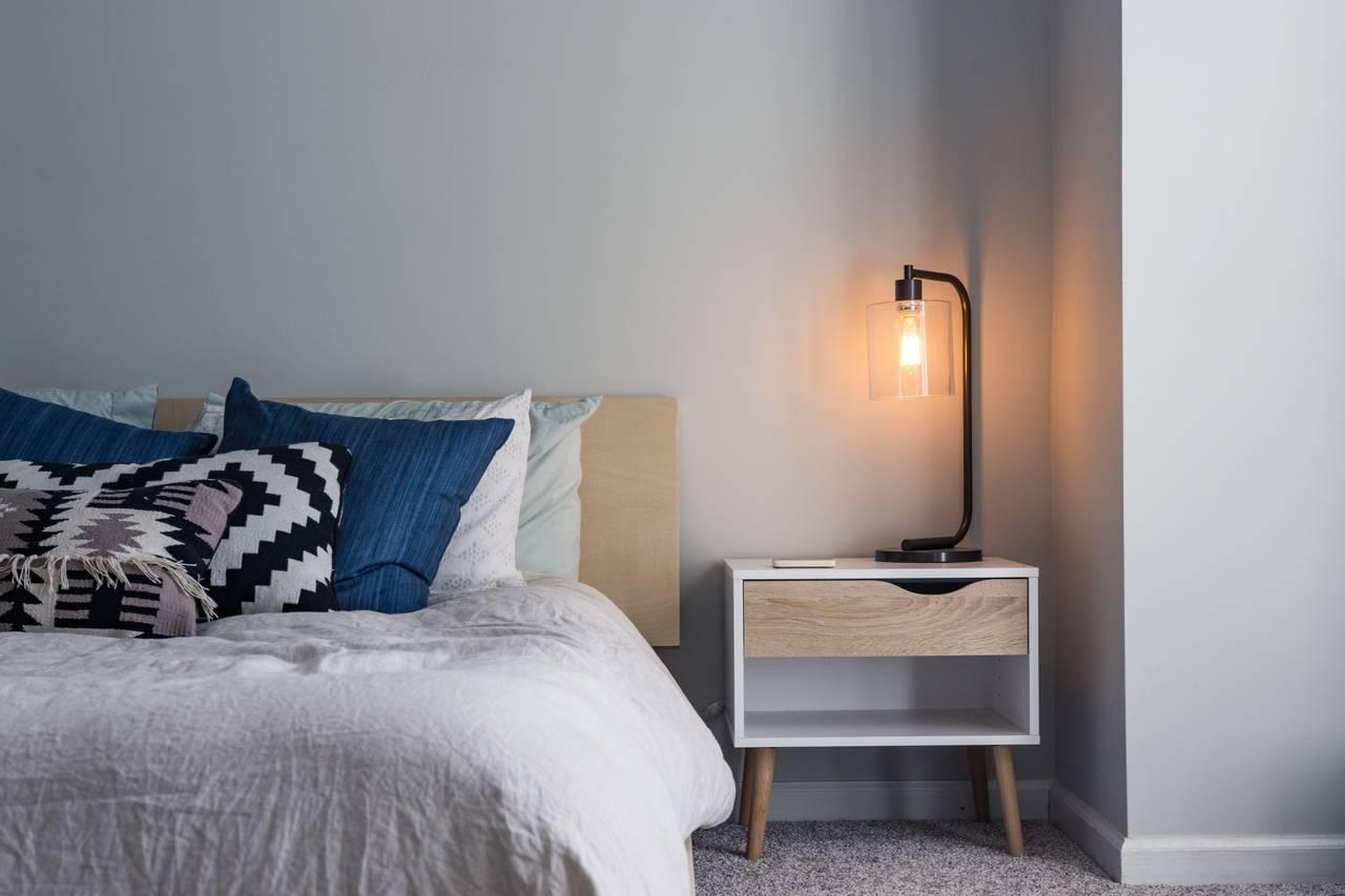 stolik nocny z lampką obok łóżka