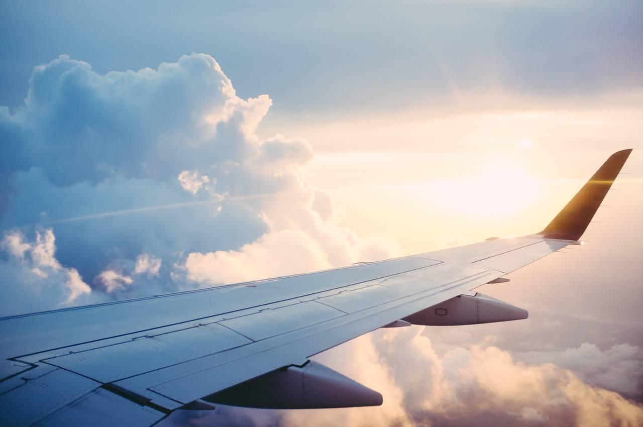 Widok z wnętrza samolotu na skrzydło i zachodzące słońce