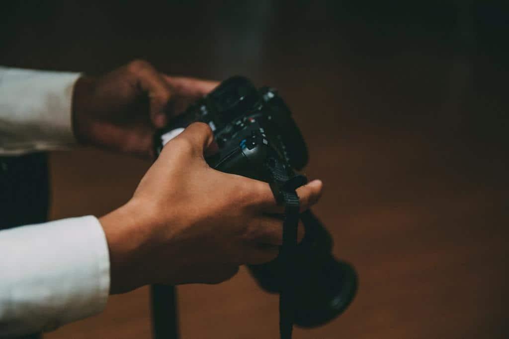 fotograf na weselu patrzy na zrobione zdjęcie