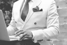 Mężczyzna w garniturze korzysta z laptopa do obliczania podatków