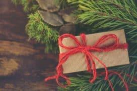 Gustownie zapakowany prezent leży podchoinką