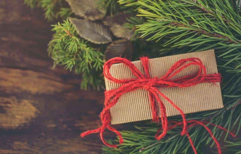 Gustownie zapakowany prezent leży pod choinką