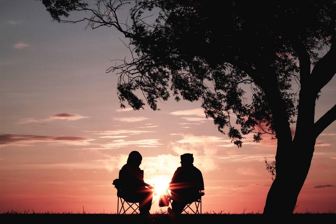 Para rozmawia opieniądzach wzwiązku natle zachodzącego słońca