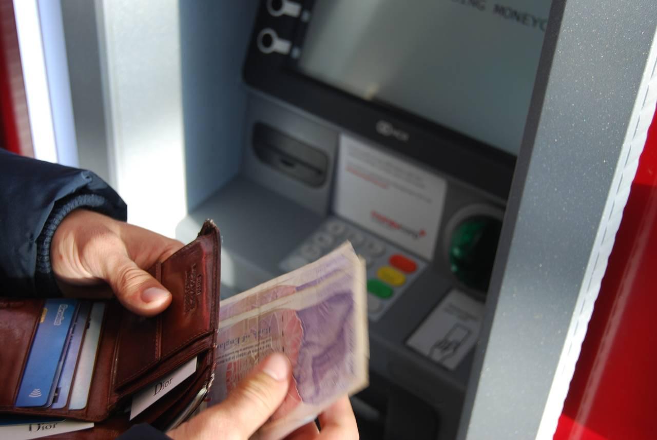 Mężczyzna wypłaca pieniądze zbankomatu