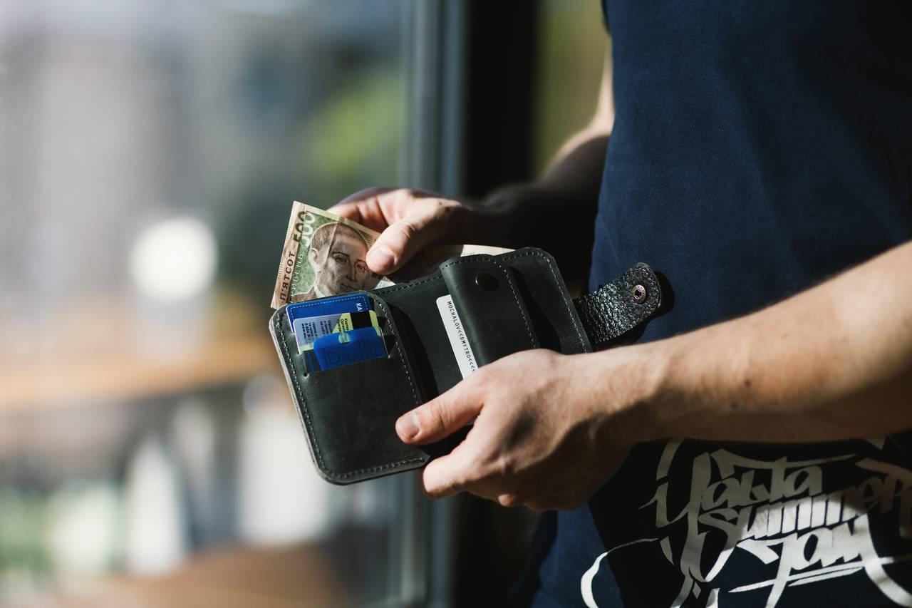 Mężczyzna sprawdza ile ma pieniędzy wportfelu