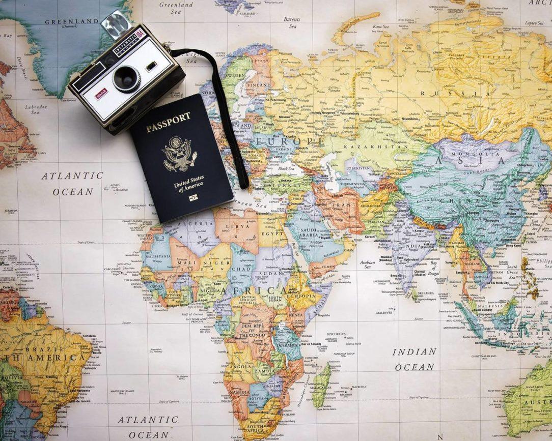 Paszport i stary aparat fotograficzny leżą na mapie świata