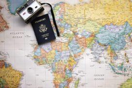 Paszport istary aparat fotograficzny leżą namapie świata