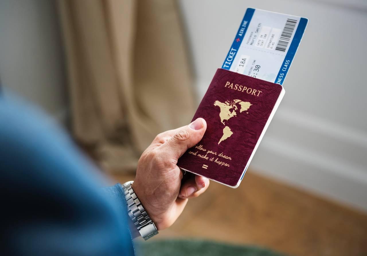 Mężczyzna trzyma paszport ibilet lotniczy