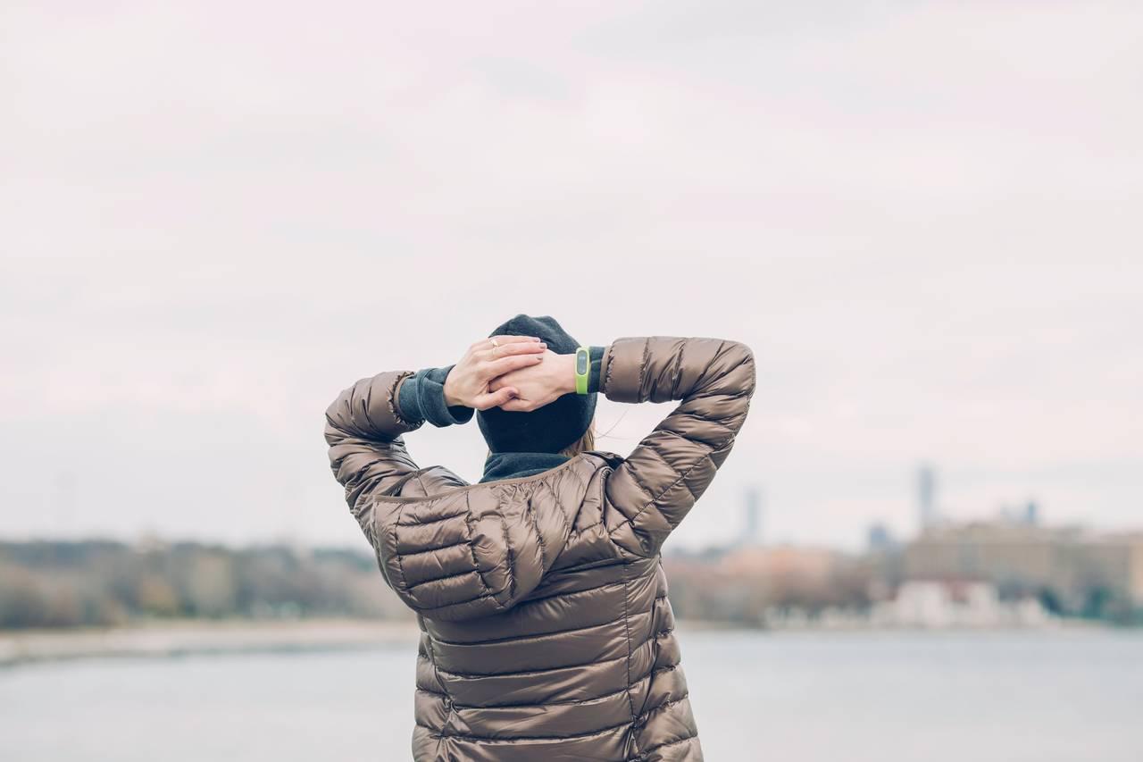 kobieta stoi nadbrzegiem rzeki itrzyma ręce nagłowie