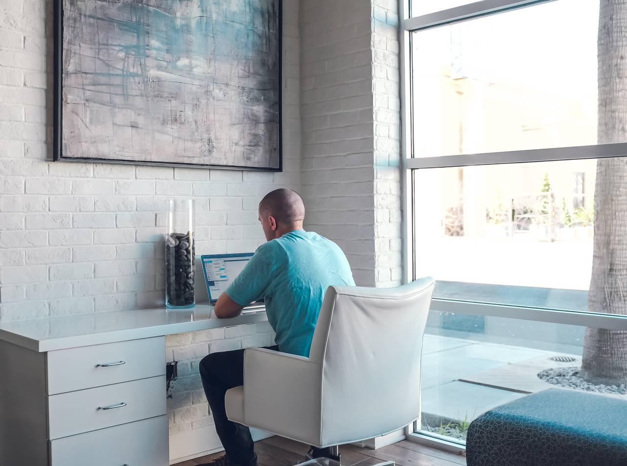 Mężczyzna siedzi przy komputerze iszuka ofert last minute