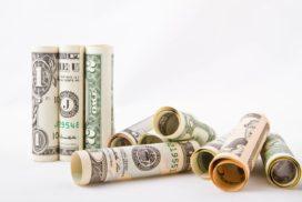 Zwinięte wrulony dolary symbolizujące mity dotyczące oszczędzania pieniędzy
