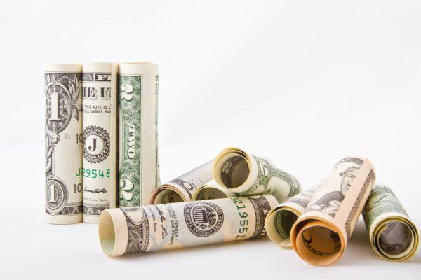 Zwinięte w rulony dolary symbolizujące mity dotyczące oszczędzania pieniędzy