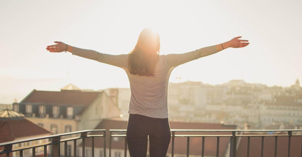 kobieta stoi na balkonie i symbolizuje zasady racjonalnego wydawania pieniędzy