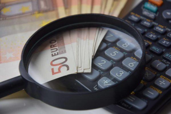 Lupa, pieniądze i kalkulator jako symbole analizy swoich finansów i zasad oszczędzania