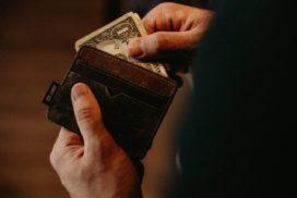 Mężczyzna wyciąga pieniądze zportfela stosując zasady racjonalnego wydawania pieniędzy