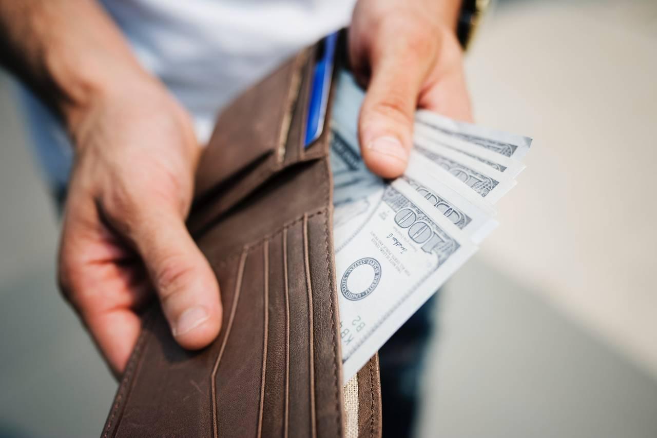 Mężczyzna trzyma portfel pełen gotówki jako symbol zasady racjonalnego wydawania pieniędzy