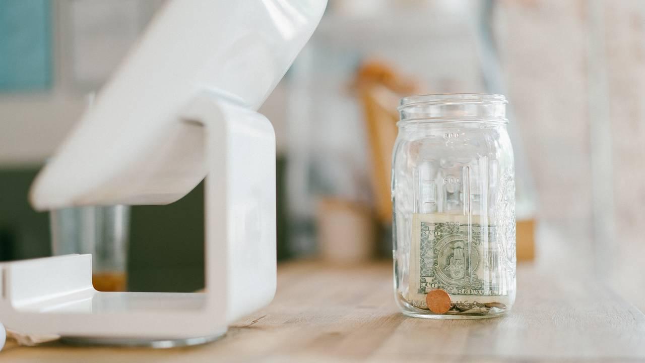 Słoik z oszczędnościami stojący na stole ja rozwiązanie błędów finansowych związanych z brakiem oszczędności