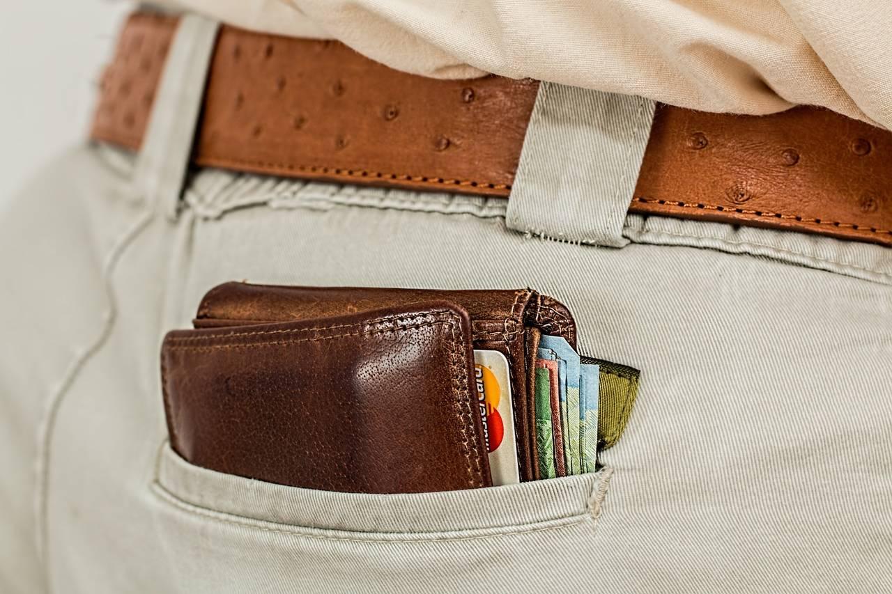 portfel pełen pieniędzy schowany dotylniej kieszeni spodni