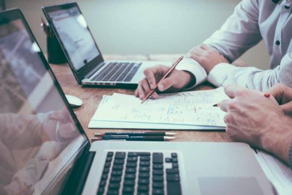 Dwóch mężczyzn siedzi przy biurku i analizuje zdolność kredytową dla banku