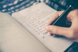 Kobieta zaznacza dobre nawyki finansowe wswoim zeszycie