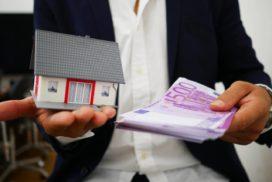 Mężczyzna trzyma wdłoniach pieniądze orazdom jako symbol dobrej historii kredytowej