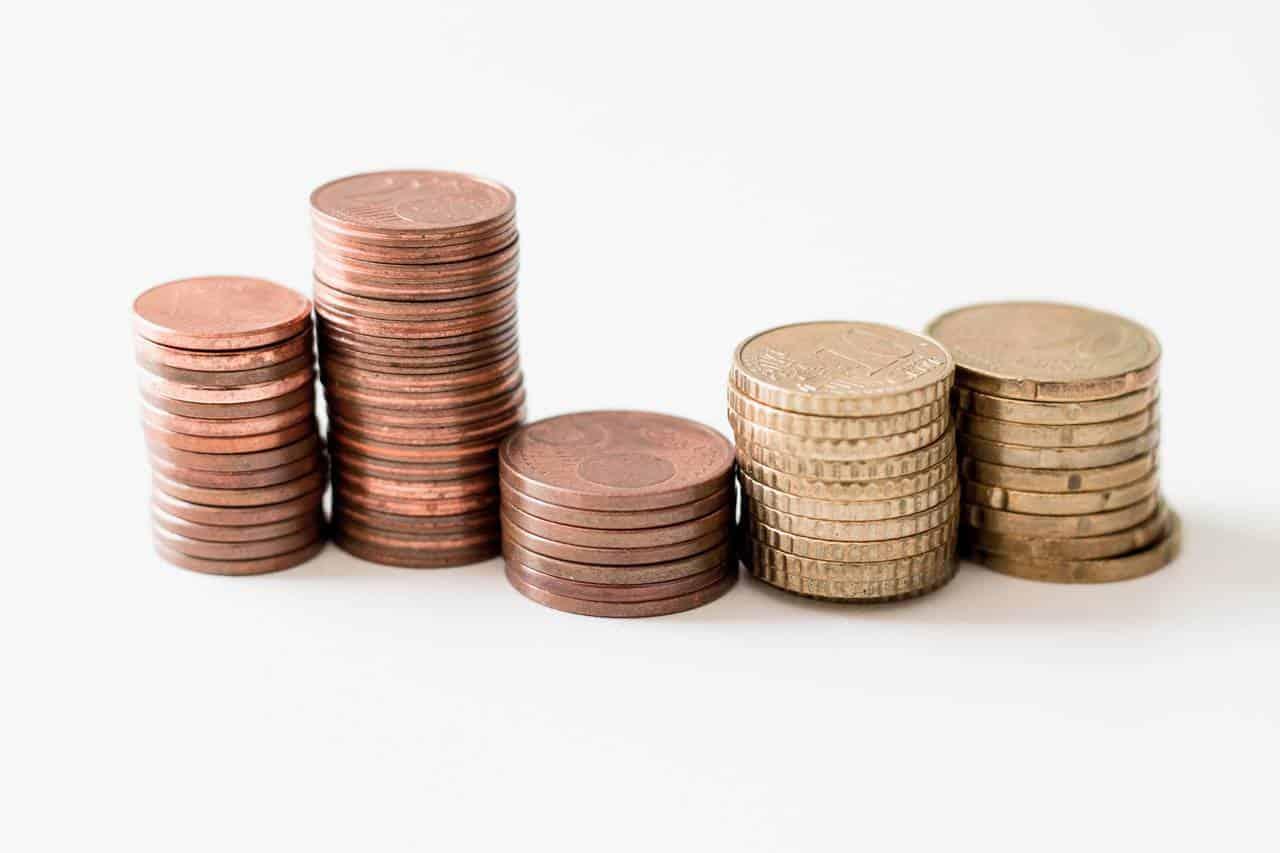 monety ułożone jedne nadrugiej jako symbol małych kwot drążących kieszeń