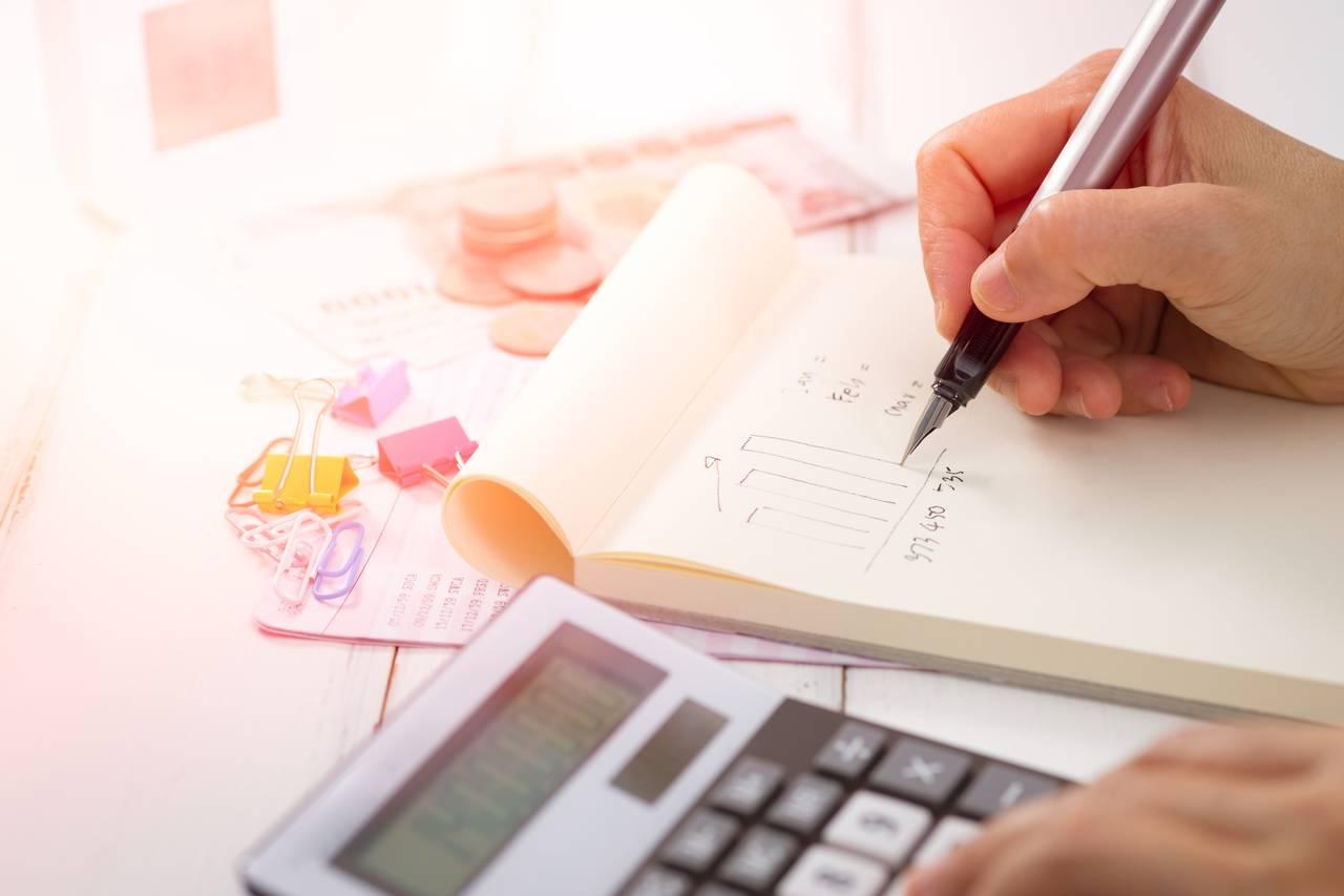Mężczyzna trzyma wręce pióro izastanawia się dlaczego warto prowadzić budżet domowy