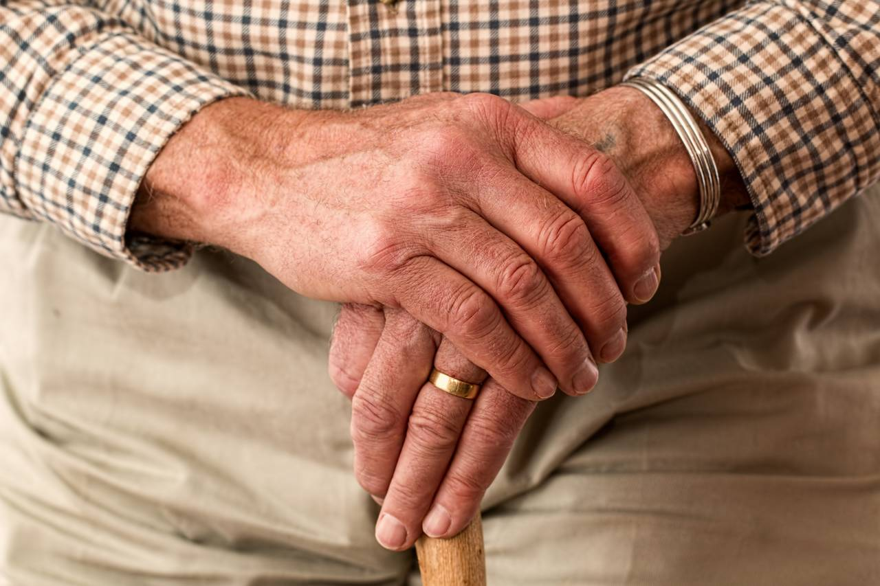 Dłonie starszego mężczyzny jako symbol noworocznego postanowienia finansowego związanego zodkładaniem naemeryturę