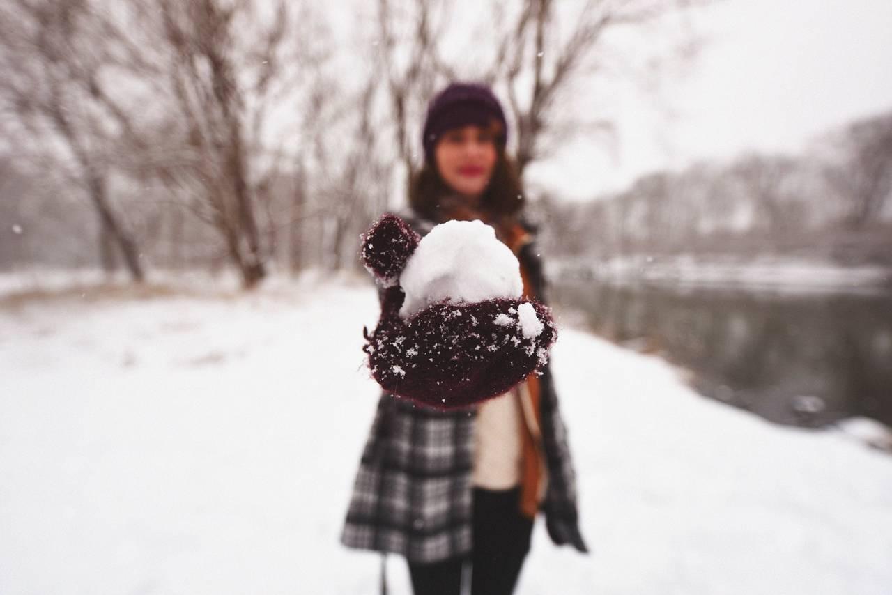 Kobieta trzyma kule śnieżną jako symbol radzenia sobie zdługami