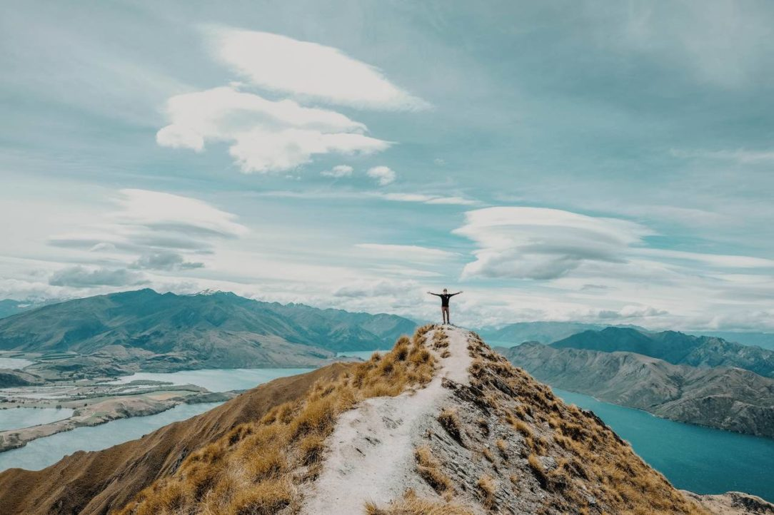Osoba stojąca na szycie góry jako symbol zmotywowania się do oszczędzania