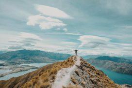 Osoba stojąca naszycie góry jako symbol zmotywowania się dooszczędzania