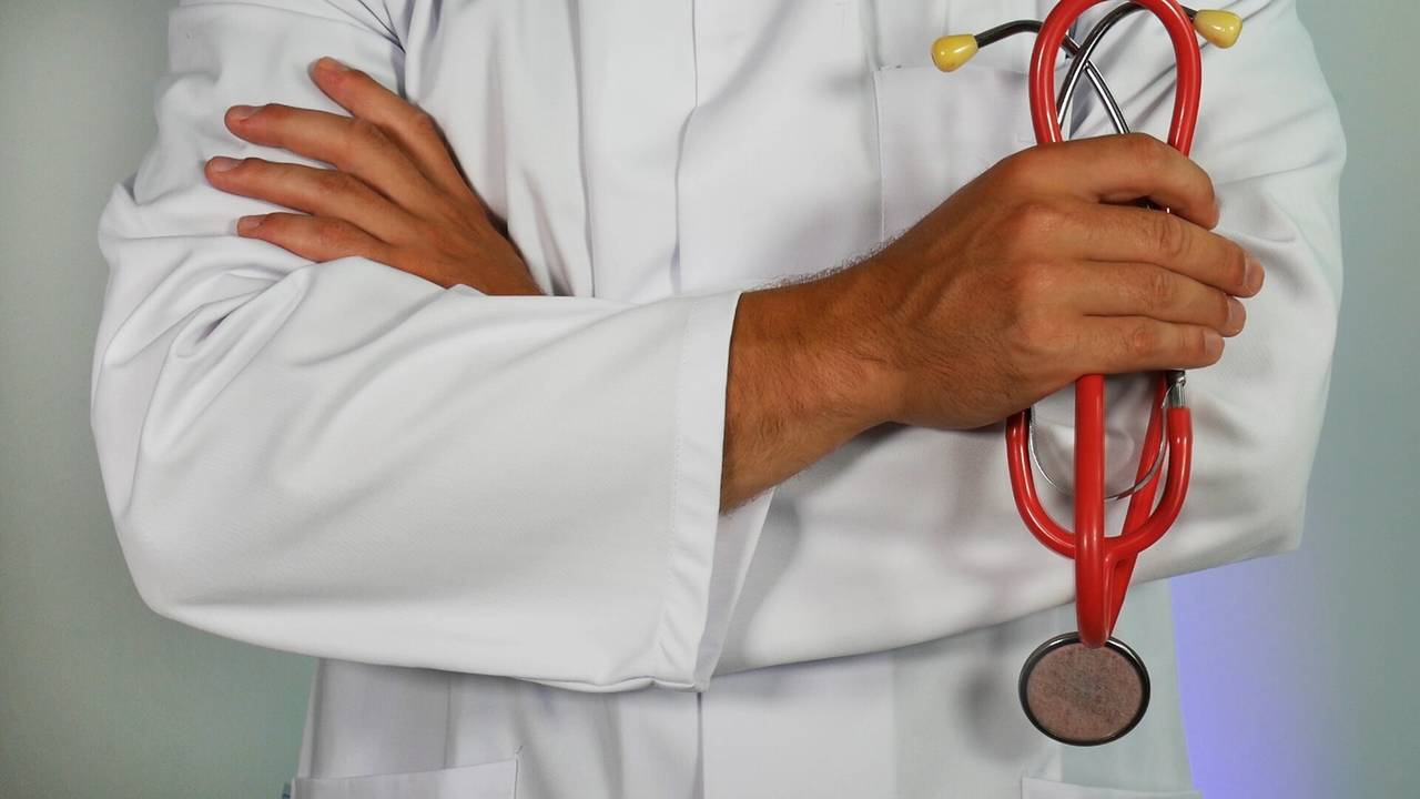 Lekarz trzymający stetoskop przypominający, żeniewarto oszczędzać pieniędzy nawłasnym zdrowiu