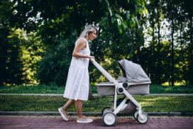 Mama prowadzi wózek dziecięcy poparku