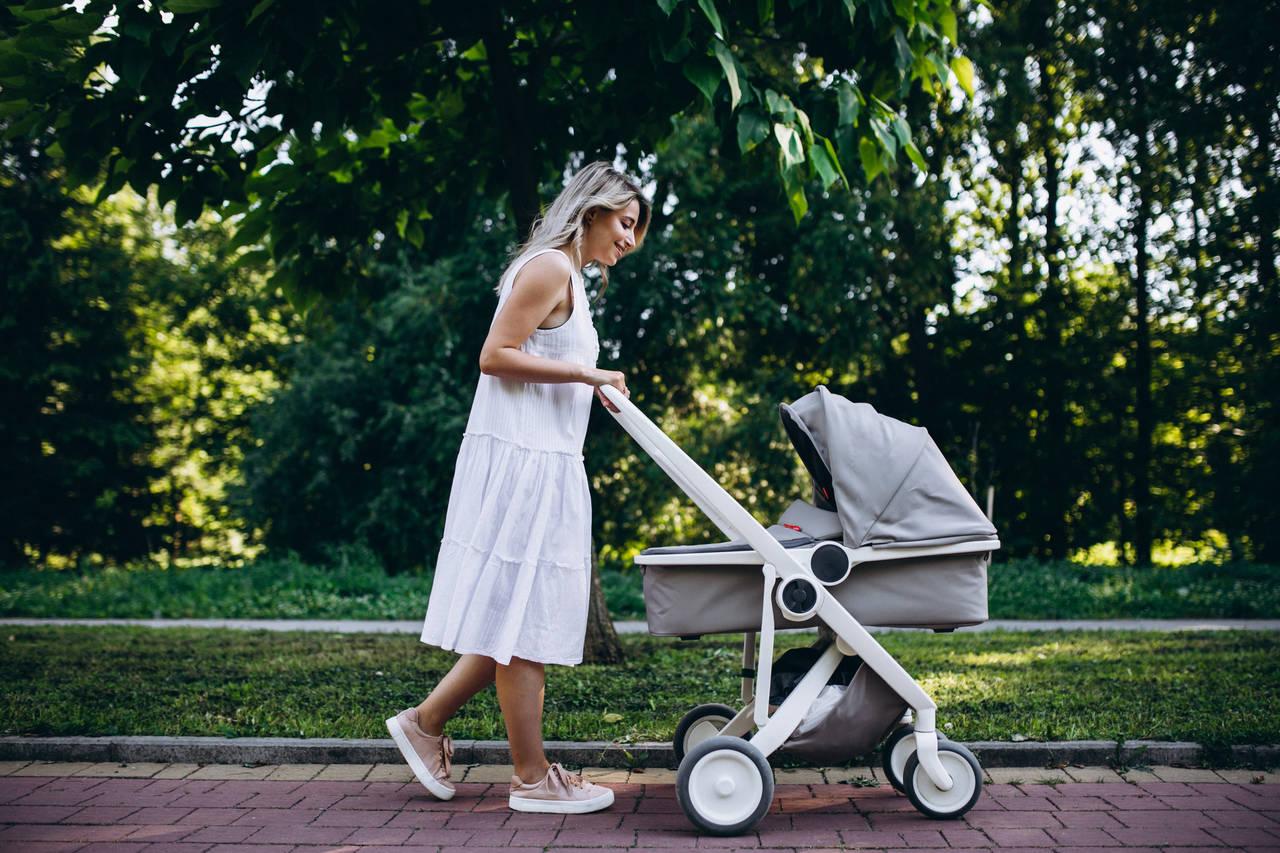 Mama prowadzi wózek dziecięcy po parku