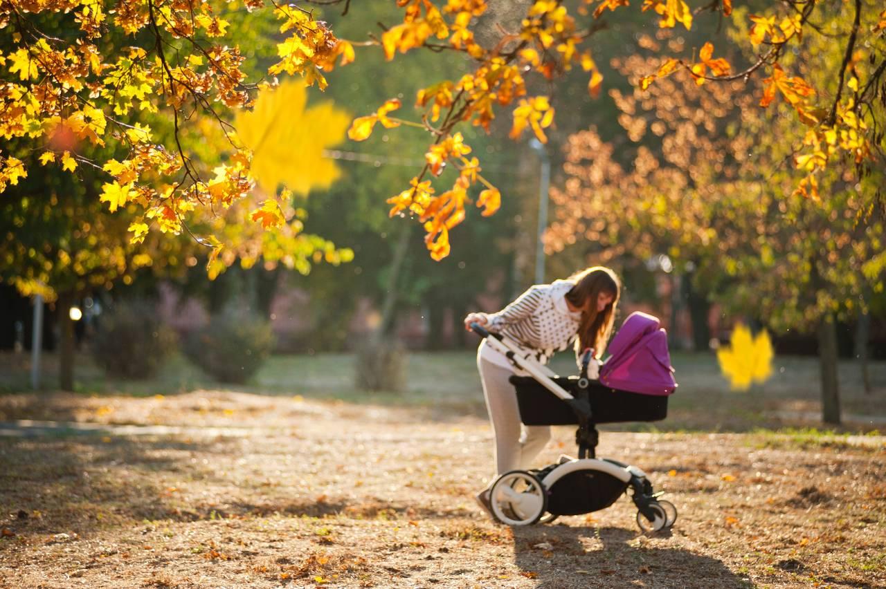 Kobieta zagląda doswojego dziecka siedzącego wwózku dziecięcym