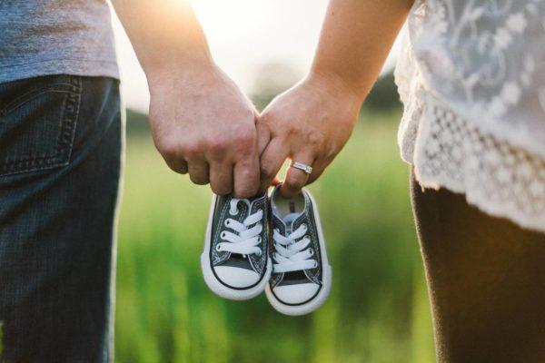 Para trzyma parę małych butów dziecięcych jako symbol przygotowań siebie i finansów domowych na narodziny dziecka