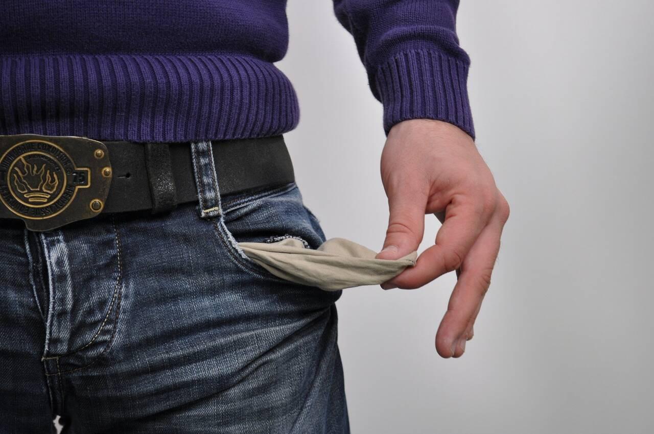 Mężczyzna pokazuje pustą kieszeń jako wynik tego do czego może doprowadzić nieświadome marnowanie pieniędzy
